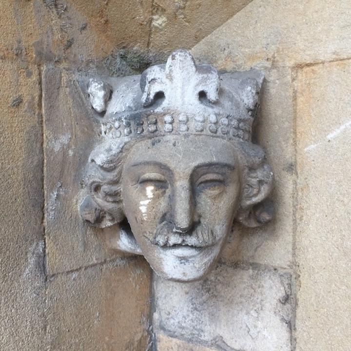 Stone carving of a male head with a crown