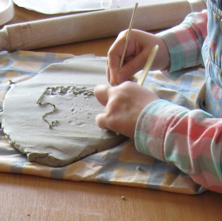 A child working on air drying clay