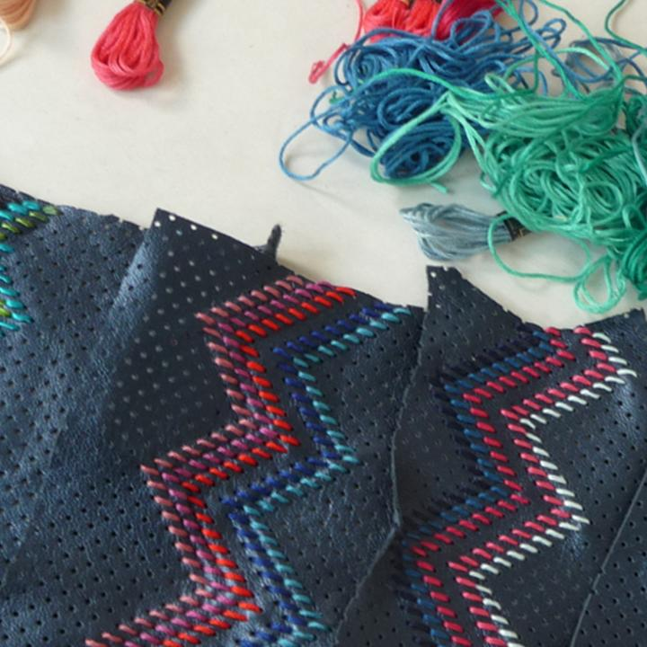 Blue fabric embroidered with different coloured threads